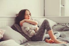 使用与玩具熊的愉快的孩子女孩在她的屋子里,坐床 库存照片