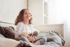 使用与玩具熊的愉快的孩子女孩在她的屋子里,坐床 免版税库存照片
