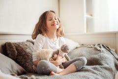 使用与玩具熊的愉快的孩子女孩在她的屋子里,坐床 库存图片