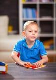 使用与玩具的儿童男孩在桌上 免版税库存图片