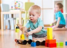 使用与玩具的儿童男孩在游戏室抬头 免版税库存照片