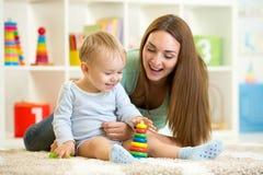 使用与玩具的小孩和他的妈妈 免版税库存照片