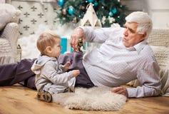 使用与玩具的小孩男孩和他的祖父 库存照片