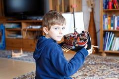 使用与玩具的小白肤金发的学龄前孩子男孩运送户内 免版税库存照片