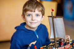 使用与玩具的小白肤金发的学龄前孩子男孩运送户内 免版税图库摄影