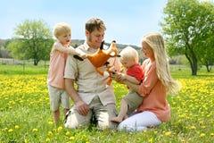 使用与玩具的愉快的四口之家人外面在花 库存图片