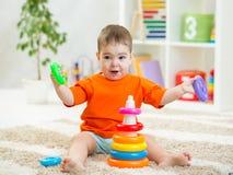 使用与玩具的滑稽的婴孩在幼儿园 免版税图库摄影