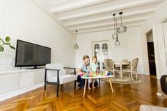 使用与玩具的父亲和小男孩在屋子里 免版税图库摄影