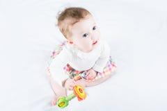 使用与玩具的甜女婴坐一条白色毯子 免版税库存图片