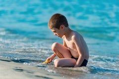 使用与玩具的美丽的男孩在海边 库存照片