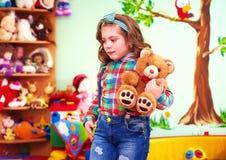 使用与玩具的逗人喜爱的女孩在孩子的幼儿园与特别需要 库存照片