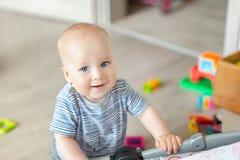 使用与玩具的逗人喜爱的男婴画象在托儿所 在家微笑可爱的孩子 免版税库存照片