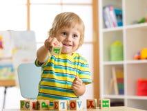 使用与玩具立方体和记住信件的小学龄前儿童儿童男孩 早期的教育概念 图库摄影