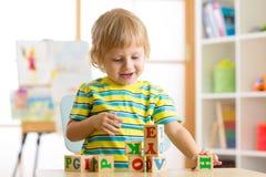 使用与玩具立方体和记住信件的小学龄前儿童儿童男孩 早期的教育概念 免版税库存图片