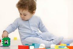 使用与玩具立方体的可爱的一个岁孩子 库存图片