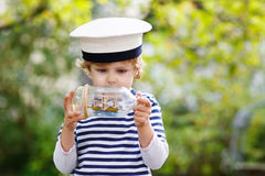 使用与玩具船的船长制服的愉快的孩子男孩 图库摄影