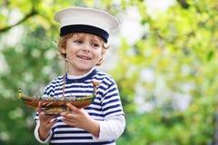 使用与玩具船的船长制服的愉快的孩子 免版税库存照片