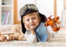 使用与玩具飞机和作梦成为的愉快的儿童小孩飞行员 库存照片