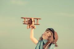 使用与玩具飞机的愉快的孩子反对夏天天空 免版税库存图片