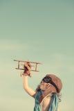 使用与玩具飞机的愉快的孩子反对夏天天空 库存照片