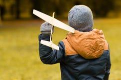 使用与玩具飞机的愉快的小男孩户外 免版税库存图片
