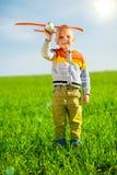 使用与玩具飞机的愉快的男孩反对蓝色夏天天空和绿色领域背景 免版税图库摄影