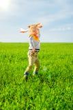 使用与玩具飞机的愉快的男孩反对蓝色夏天天空和绿色领域背景 免版税库存照片