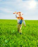 使用与玩具飞机的愉快的男孩反对蓝色夏天天空和绿色领域背景 图库摄影