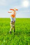 使用与玩具飞机的愉快的男孩反对蓝色夏天天空和绿色领域背景 库存照片