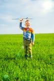 使用与玩具飞机的愉快的男孩反对蓝色夏天天空和绿色领域背景 免版税库存图片