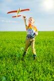 使用与玩具飞机的愉快的男孩反对蓝色夏天天空和绿色领域背景 库存图片