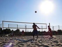 使用与球和太阳的沙子晴朗的沙滩排球人在背景,科沙林,波兰, 2018年8月中 图库摄影