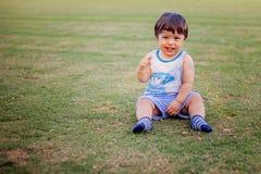 使用与球和玩具的愉快的男孩在绿草 库存照片