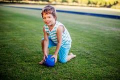 使用与球和玩具的愉快的男孩在绿草 免版税库存图片