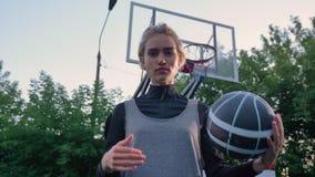 使用与球和看照相机的可爱的白肤金发的女性蓝球运动员,站立在公园,白天 影视素材