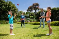 使用与球的愉快的家庭在公园 库存照片