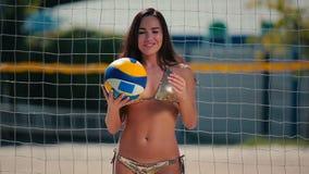 使用与球的年轻美丽的女孩在手上在海滩的网附近 股票录像