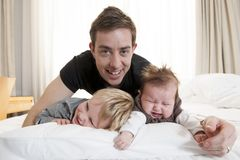 使用与甜女婴和儿子的年轻父亲 免版税库存图片
