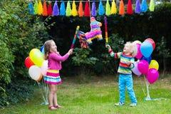 使用与生日彩饰陶罐的孩子 库存照片