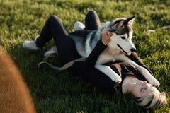 使用与用不同的眼睛的滑稽的多壳的狗的美丽的少妇户外在公园 免版税库存图片