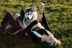 使用与用不同的眼睛的滑稽的多壳的狗的美丽的少妇户外在公园 免版税库存照片