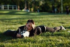 使用与用不同的眼睛的滑稽的多壳的狗的美丽的少妇户外在公园 图库摄影