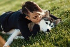 使用与用不同的眼睛的滑稽的多壳的狗的美丽的少妇户外在绿草的公园 免版税库存图片