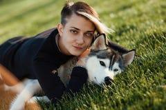 使用与用不同的眼睛的滑稽的多壳的狗的美丽的少妇户外在绿草的公园 图库摄影