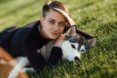使用与用不同的眼睛的滑稽的多壳的狗的美丽的少妇户外在绿草的公园 免版税库存照片