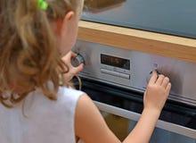 使用与电烤箱的孩子 免版税库存照片