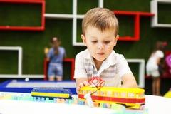 使用与电车的逗人喜爱的男孩 使用与汽车玩具的小男孩 库存图片