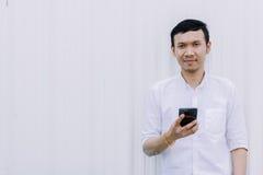 使用与白色墙壁的亚裔人手机微笑 免版税库存图片