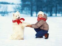 使用与白色萨莫耶特人狗的愉快的少年男孩户外在公园在一个冬日,正面狗给爪子所有者 库存图片