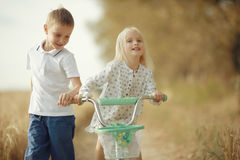 使用与秋天路的一个女孩的男孩 免版税库存图片